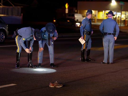 Delaware State Police officers investigate at the scene