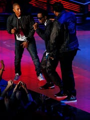 Pharrell Williams, left, Diddy, and Busta Rhymes perform