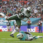 Jets defensive back Darrelle Revis makes an interception over Miami's Jarvis Landry at Wembley stadium in London, Sunday, Oct. 4, 2015.