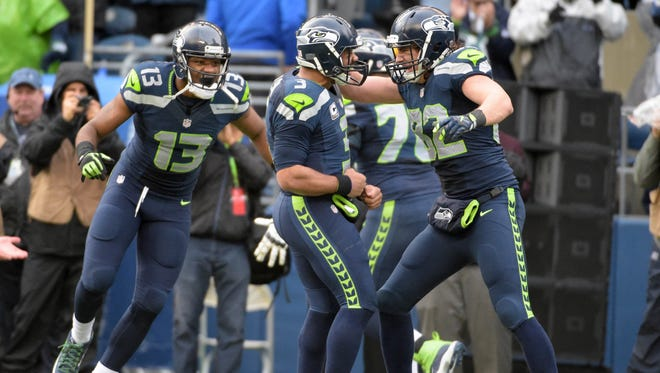 Russell Wilson, center, celebrates with tight end Luke Willson, right, after the Seahawks scored on a two-point conversion late in the fourth quarter.