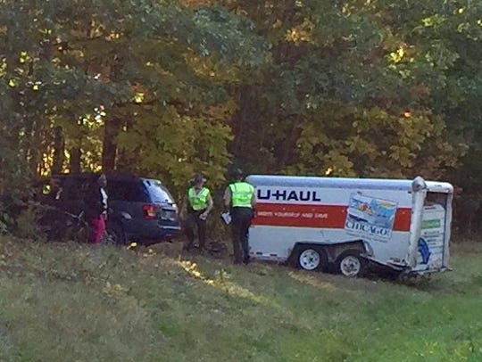 A vehicle towing a U-Haul trailer is in the trees on