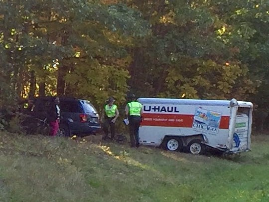 A vehicle towing a U-Haul trailer is in the trees on the east side of Interstate 89 near Exit 16 in Colchester. The accident slowed traffic Monday, Oct. 12, 2015, morning.