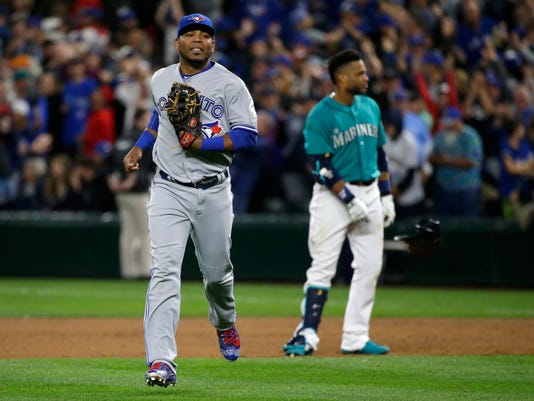 Toronto Blue Jays first baseman Edwin Encarnacion, left, runs to the dugout after Seattle Mariners' Robinson Cano, right, lined out to right field with the bases loaded to end the eighth inning of a baseball game, Monday, Sept. 19, 2016, in Seattle. (AP Photo/Ted S. Warren)