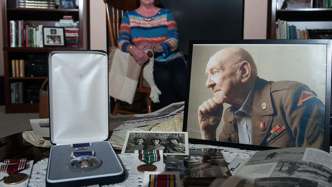 Christine Mallon shows the war medals and relics of her late uncle Theodore Paluch at her home in Delran. Mallon received posthumous medals Monday for her uncle, a World War II Army veteran who survived the Malmedy Massacre of U.S. servicemen by a German SS Panzer unit during the Battle of the Bulge in 1944 in Belgium.