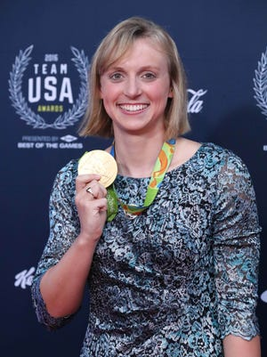 Olympic swimmer Katie Ledecky shows one of her gold medals while walking the red carpet at the Team USA Awards at Georgetown University on Sept. 28.