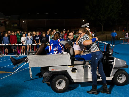 Matthew Rhodes (32) watches as Gabby Smith, 12, hugs her 17-year-old brother, Evan Smith, a senior linebacker for Memphis University School, after he received an injury during the game against Briarcrest at Hull-Dobbs Field on Friday. Smith said she felt really sad because the older Smith really loves football.