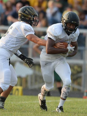 Winchester's Austin Lawrence hands the ball off to Kiante Enis against Northeastern during a football game Friday, Aug. 28, 2015 in Fountain City.