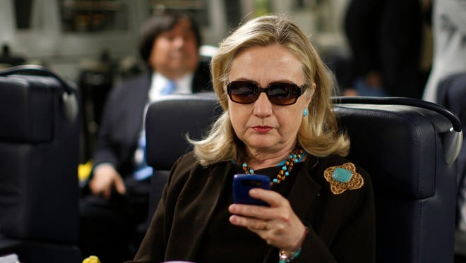 In this Oct. 18, 2011, file photo, then-secretary of State Hillary Clinton checks her BlackBerry from a desk inside a C-17 military plane.