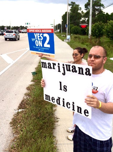 "Michelle DeRhodes  and Ryan Kuhn wave to passersby as they hope to change a few minds to ""yes"" on medical marijuana Amendment 2 Tuesday in Fort Myers. Marijuana helps Michelle with her epileptic seizures."
