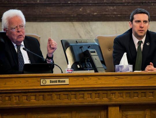 Council members David Mann and P.G. Sittenfeld listen