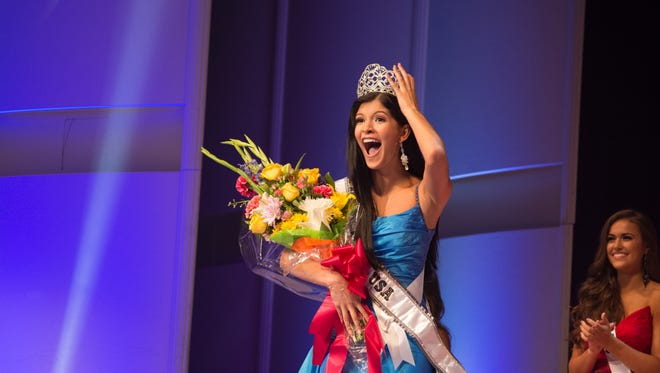 Sophia Dominguez-Heithoff holds a bouquet of flowers as she celebrates her win.