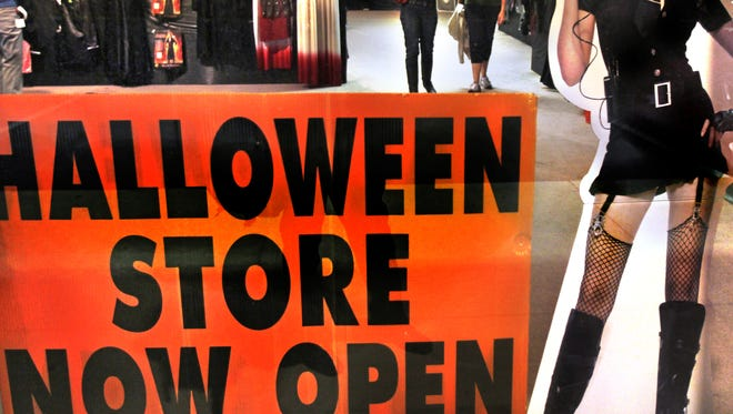 A cutout of a woman in a Halloween costume stands in the window of a Halloween store.