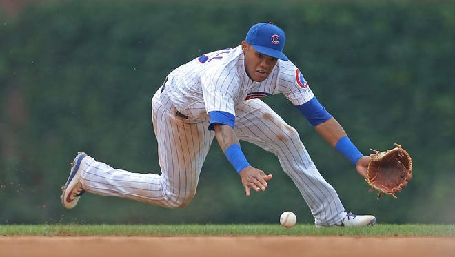 Chicago Cubs shortstop Addison Russell  fields an infield hit off the bat of St. Louis Cardinals second baseman Yairo Munoz during the ninth inning at Wrigley Field in Chicago.