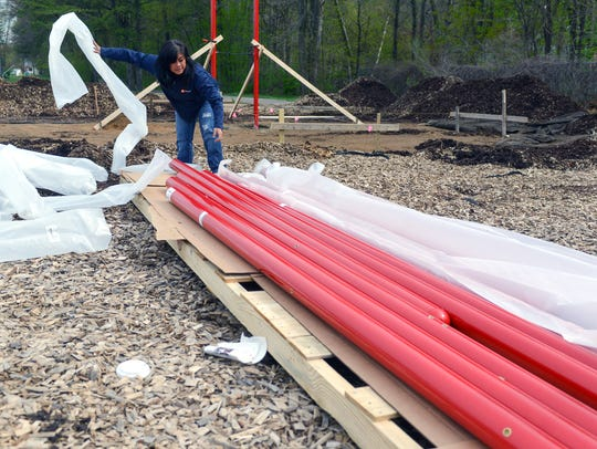Crystal Baumann unwraps the poles that will be used