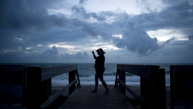 """Susan Carvell (pictured) and her husband Stan visited Humiston Park at sunrise to check out conditions before Hurricane Matthew on Oct. 6, 2016, in Vero Beach. """"We don't live at the beach. We live inland,"""" Susan said. """"We have shutters up and everything, so we're all set."""" Stan added, """"The worst this is no electricity afterward."""""""
