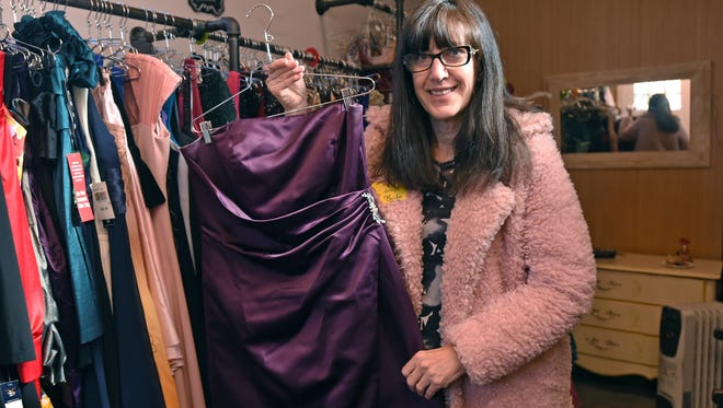 Barbie Marcoe shows a prom dress inside the trailer from where she donates the prom clothing to young homeless teens or teens in foster care.