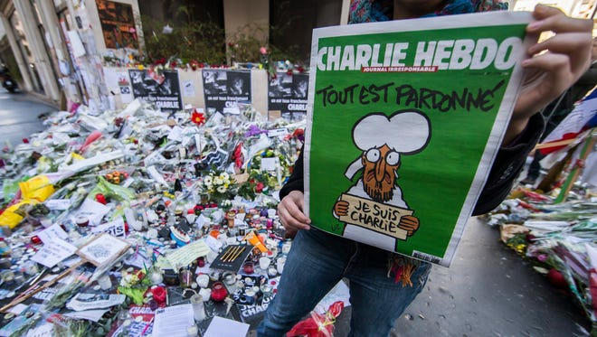 "A woman holds the new edition of the French satirical magazine ""Charlie Hebdo"" in front of the improvised memorial on Rue Nicolas Appert, near the ""Charlie Hebdo"" headquarters in Paris on Jan. 14, 2015."
