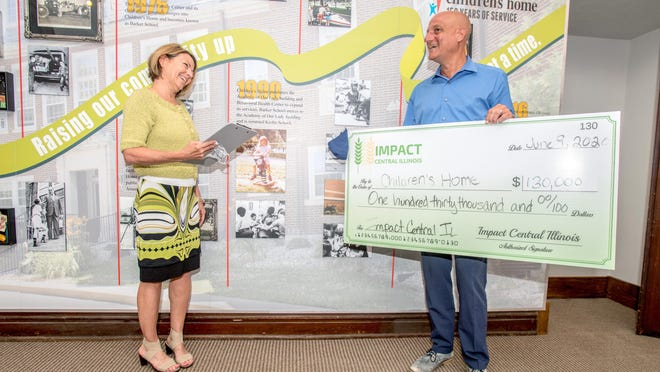 Shelley Weaver, vice-president of Impact Central Illinois, shares some kind words with Children's Home CEO Matt George during a check presentation Tuesday, June 9, 2020 at Children's Home, 2130 Knoxville Avenue, in Peoria. The philanthropic women's organization raised $130,000 for charity and awarded a grant from a list of qualified applicants through a membership vote.