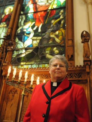 The Rev. Deborah Hafner DeWinter, pastor at the First Evangelical Lutheran Church in the City of Poughkeepsie, stands in front of a stained glass window depicting the resurrection of Jesus Christ, which is celebrated on Easter Sunday.