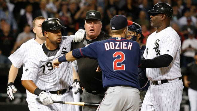 Minnesota Twins' Brian Dozier (2) comes off the bench and pushes Chicago White Sox's Jose Abreu (79) after Abreu was hit by a pitch from relief pitcher Trevor May during the eighth inning of a baseball game Friday, May 6, 2016, in Chicago. Watching the play are Todd Frazier, left, catcher Kurt Suzuki and first base coach Daryl Boston, right (AP Photo/Charles Rex Arbogast)