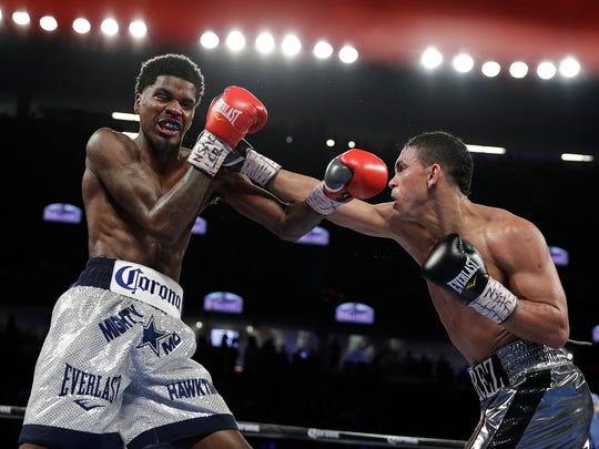 Maurice Hooker, left, is hit by Darleys Perez, of Colombia, during their boxing bout Saturday, Nov. 19, 2016, in Las Vegas.