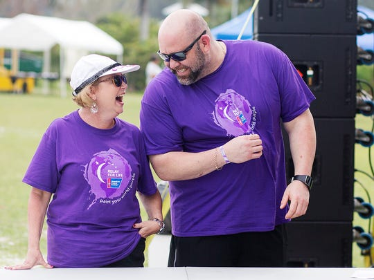 Cancer survivors Teresa Miller and Larry Chapman play the 'Price is Right' game during the Fort Myers Relay for Life festival Saturday at Lakes Regional Park.