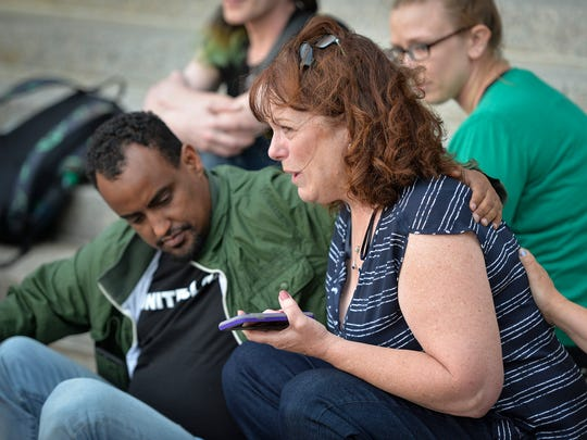 Jane Conrad is comforted by local muslim community leader Haji Yusuf as she cries for the victims of the Florida nightclub shooting during a vigil Sunday, June 12, at the Stearns County Courthouse.