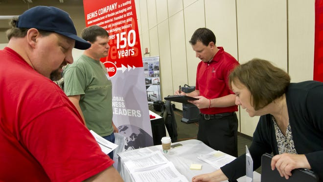 Pam Hensen of Bemis Co. points out to Aaron Bohn the company's job opportunities during a June 6, 2013, job fair at the Oshkosh Convention Center.