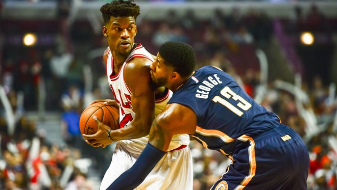 Chicago Bulls guard Jimmy Butler (21) is defended by Indiana Pacers forward Paul George (13) during the first half of Saturday's game at the United Center.