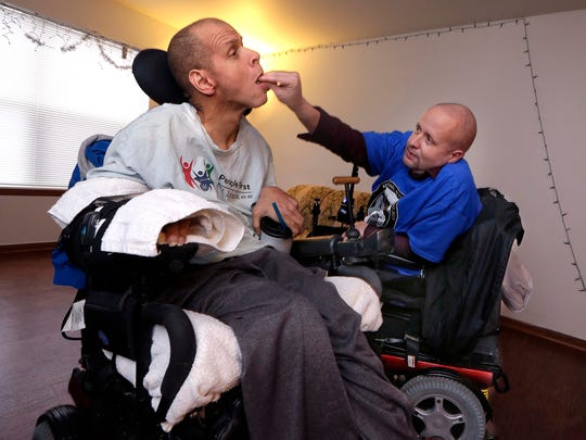 Larry Brown places Mark Hubbard's medications into his mouth. Larry, a paraplegic, serves as caregiver to Mark, a quadriplegic.