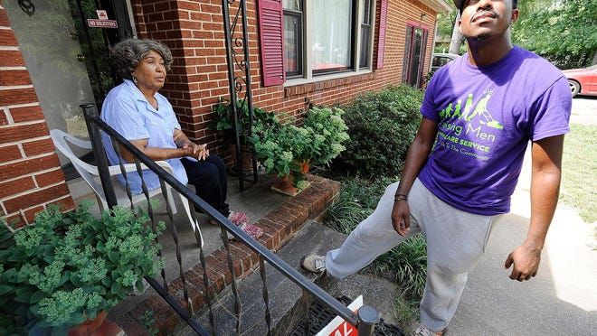 Rodney Smith Jr., founder of Raising Men Lawn Care Service, looks skyward while talking with homeowner Irene Renee Jolly in Huntsville, Ala. Inspired to provide free lawn care several years ago, Smith says he has now completed a quest to provide free lawn care for veterans in every U.S. state.