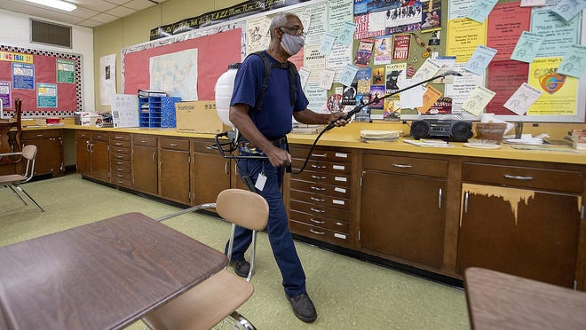 Lloyd Edmonds, of Cinnaminson, member of the maintenance staff at Delran High School, sprays a disinfectant throughout a classroom, Wednesday. All New JErsey schools must offer the option for online learning come September, but most will also offer a in-school component too. Keeping the building sanitized is a priority.