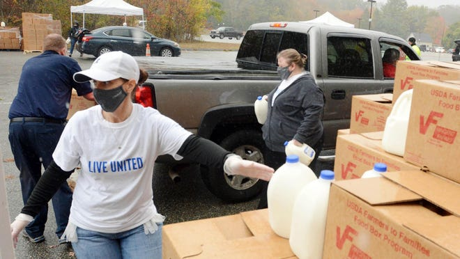 Volunteer Jenn Hess of Gales Ferry helps load food in the Farmers to Families Food Box food distribution in Norwich Friday. See videos and more photos at NorwichBulletin.com