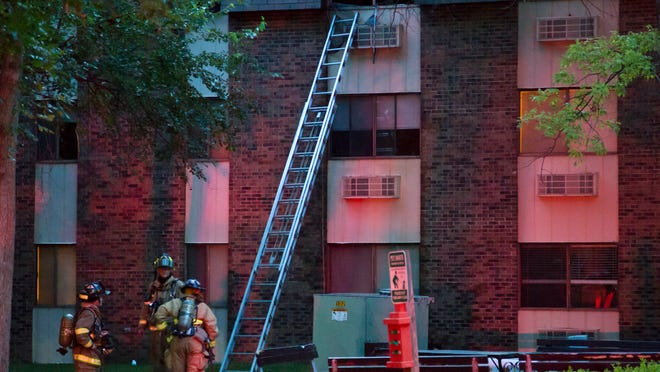 Lafayette firefighters wait Thursday at the base of a ladder after a fire at The Bluffs apartment complex in Lafayette. The fire started in a third-story apartment. The apartment's resident was taken to an area hospital.