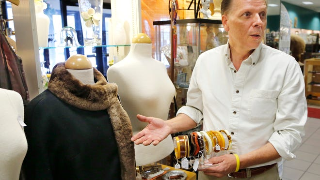 Antiques dealer John Wanat discusses Bakelite jewelry that would pair well with a '60s fall wrap with faux fur. He was at Raven's Roost Antiques in Market Square on Tuesday.