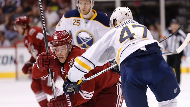 Arizona Coyotes center Joe Vitale is held up by Buffalo Sabres defender Zach Bogosian during the second period at Gila River Arena in Glendale on March 30, 2015.