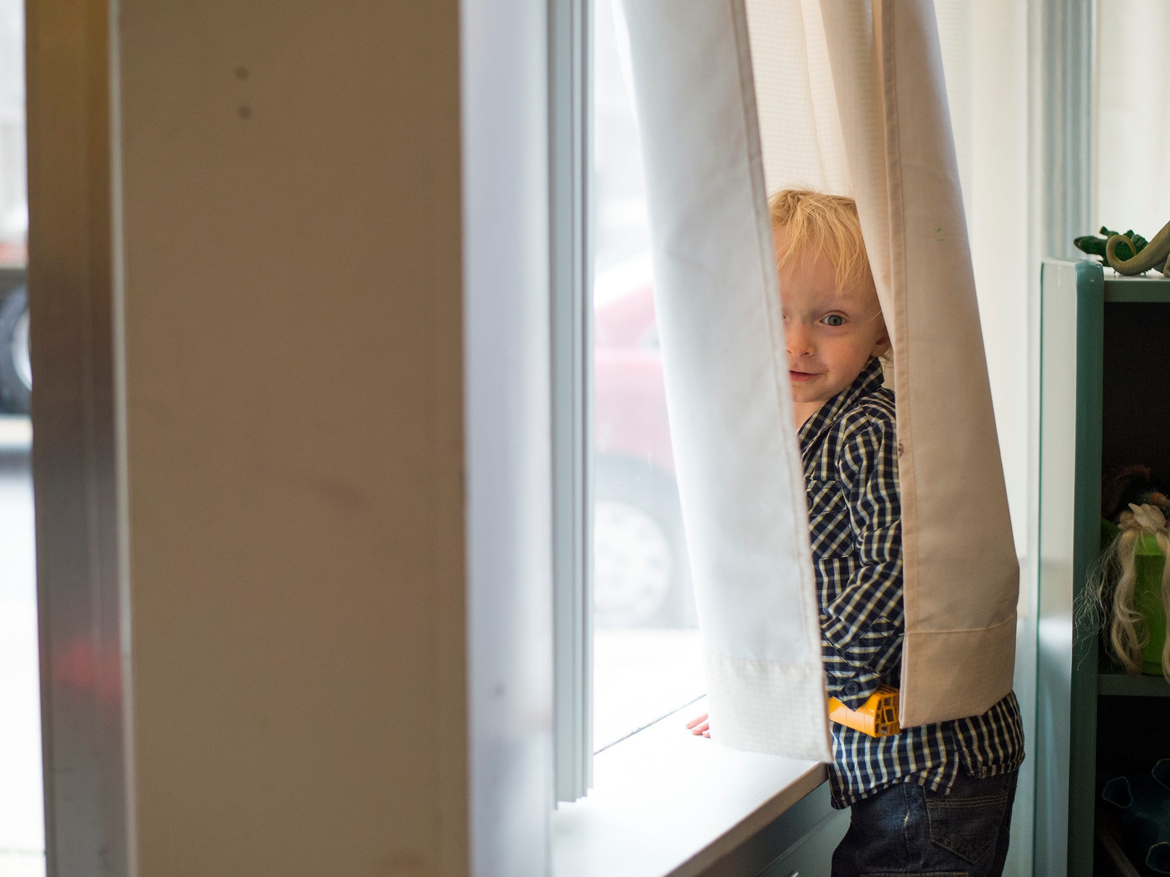 Two-year-old Eli peeks out from behind the curtains while playing at the Family Resource Center in Owego.