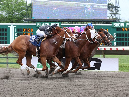 Full Salute, second from the right, puts a nose in front at the wire to win a four-horse photo finish in an allowance race Sunday at Monmouth Park in Oceanport.