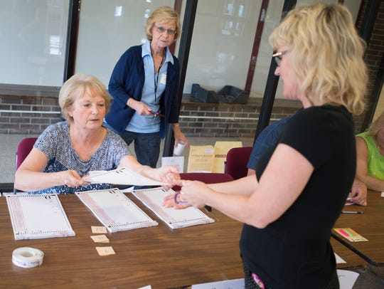 Poll worker Diane Horton, of Endwell, hands out a ballot