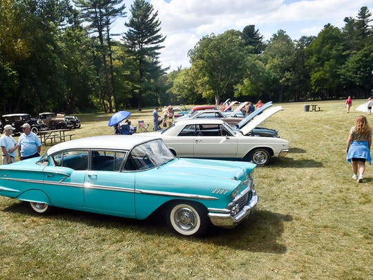 Locals walk around and look at vintage cars during