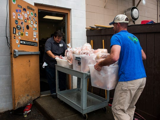 Jason Ashley helps Anthony Gray bring in several chickens into the Bacon Brothers kitchen on Monday, April 24, 2017.