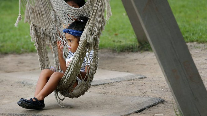 Leilani Kalapu, 2, enjoys a shaved ice from the comfort of a swinging hammock while enjoying a pleasant day at Rainbow Lake playground in Overton Park Sunday. (Mike Brown/The Commercial Appeal)