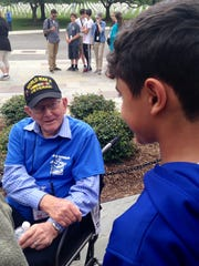 Ken Brown, a Marine veteran of the battle of Iwo Jima, talks with a youngster in Washington D.C. during the recent Utah Honor Flight trip.