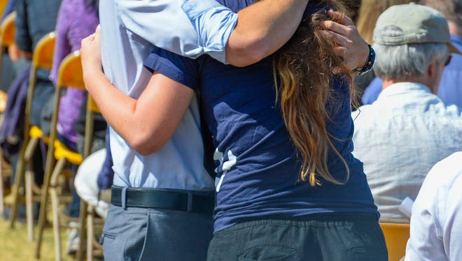 Santa Barbara, CA, U.S.A.:  Students hug before the start of a memorial service at Harder Stadium for the slain UCSB student.