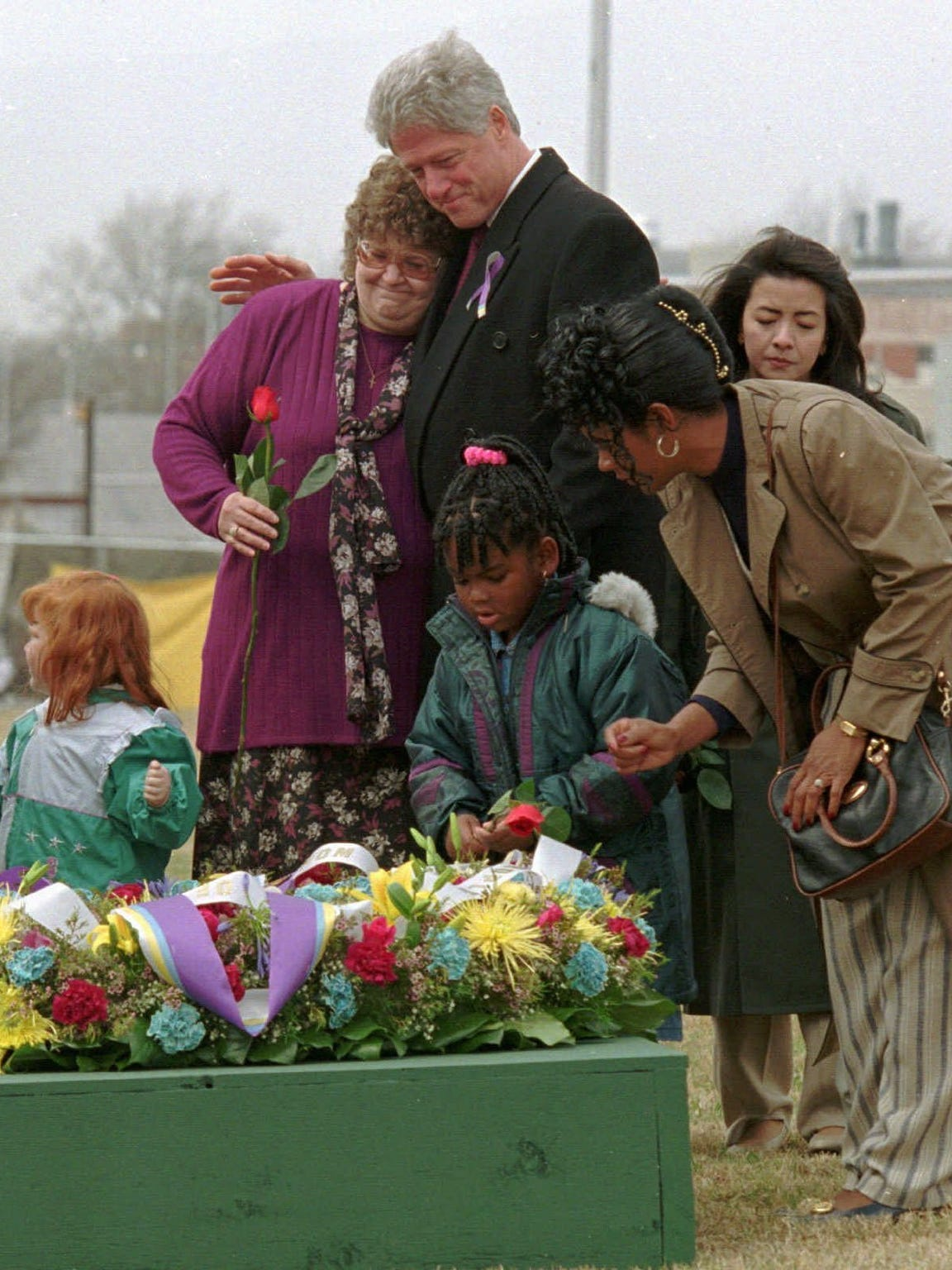 President Bill Clinton hugs Claudia Denny, mother of Rebecca Denny, left, as Nekia McCloud and her mother, Lavern McCloud, place roses on a memorial wreath on April 5, 1996, at the site of the former Alfred P. Murrah Federal Building in Oklahoma City. Both Rebecca Denny and Nekia McCloud were injured in the attack.
