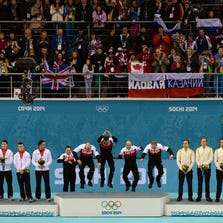 Feb 21, 2014; Sochi, RUSSIA; Gold medalists Canada (center) jumps onto the podium after being introduced between silver medalists Great Britain (left) and bronze medalists Sweden (right) in the men's curling gold medal match during the Sochi 2014 Olympic Winter Games at Ice Cube Curling Center. Mandatory Credit: Kyle Terada-USA TODAY Sports
