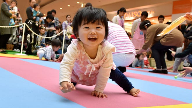 Babies compete in a baby crawling competition hosted by a Japanese magazine in 2015.