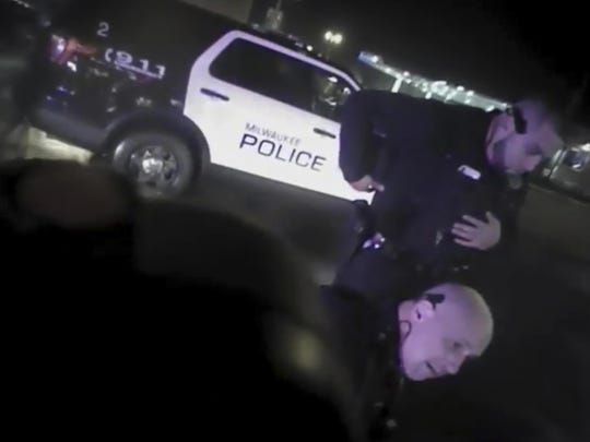 This Jan. 26, 2018, police body-camera footage released by Milwaukee Police Department shows police officers holding down Bucks guard Sterling Brown after using a stun gun in a Walgreens parking lot in Milwaukee.