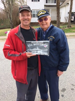 Aaron Siegler gives U.S. Navy veteran Leo Hofmeister a license plate similar to the one that was stolen from him earlier this year. Siegler delivered the plate to Hofmeister on Monday, March 26, 2018.