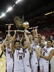 Stevens Point High School players celebrate with the trophy after defeating Arrowhead High School in the Division 1 championship game at the 2017 boys basketball state tournament at the Kohl Center on Saturday, March 18, 2017, in Madison, Wis.
